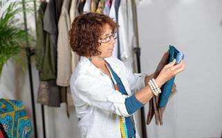 Schneiderin mittleren Alters, die in seiner Werkstatt arbeitet foto