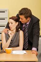 Geschäftsmann flirtet mit Geschäftsfrau im Amt foto