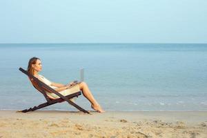 Geschäftsfrau, die am Strand arbeitet foto