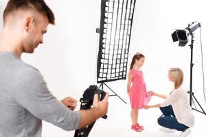 Der Fotograf überprüft seine Kamera, während das Modell vorbereitet wird foto