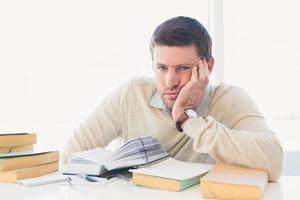 gelangweilter lässiger Geschäftsmann, der an seinem Schreibtisch studiert foto