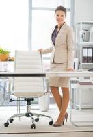Porträt der glücklichen Geschäftsfrau in voller Länge, die im Amt steht foto