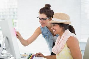 lächelnde Teamarbeit, die Computer auf Schreibtisch zeigt foto