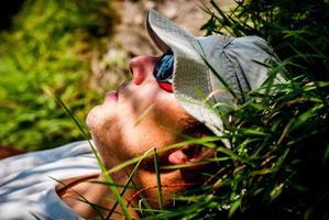 Mann, der auf dem Gras schläft, wandert foto