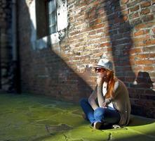 träumende hübsche Frau mit weißem Hut in einer romantischen Gasse foto