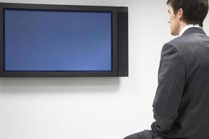 Geschäftsmann, der Flachbildfernseher betrachtet foto