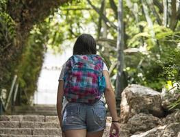Teenager-Schulmädchen mit einem Rucksack und Kopfhörern foto