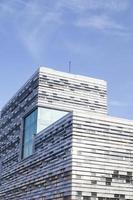 abstrakte Fassadenlinien und Glasreflexion auf modernem Gebäude