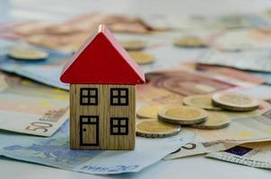 Haus, Münzen und Banknoten foto
