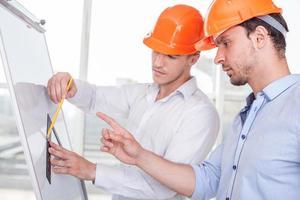 fröhliche junge Arbeiter entwerfen ein neues Gebäude