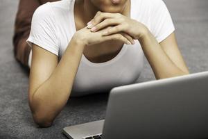 junge Frau, die beim Verwenden des Laptops liegt foto