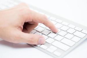 Mannhand, die auf Tastatur tippt foto