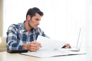 Mann sitzt am Tisch mit Rechnungen und Laptop foto