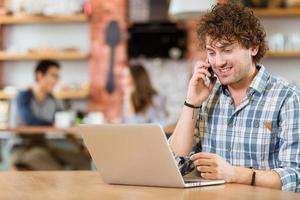 glücklicher Mann, der Laptop benutzt und auf Handy spricht foto