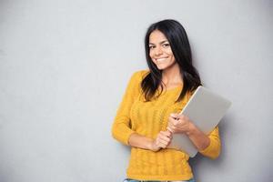 lächelnde schöne Frau, die Laptop hält foto