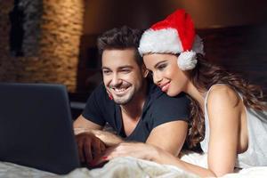 junges Paar auf der Suche nach Weihnachtsgeschenken online foto