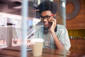 Geschäftsmann, der Telefon verwendet, das am Laptop im Kaffeehaus arbeitet