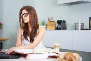 glückliche junge Frau, die in der Küche studiert
