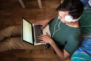 junger Mann, der an seinem Haus auf Laptop arbeitet. foto
