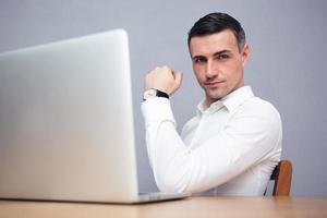 Geschäftsmann sitzt am Tisch mit Laptop