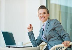 glückliche Geschäftsfrau, die am Laptop arbeitet foto