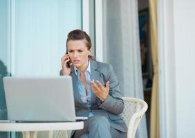 besorgte Geschäftsfrau, die Handy auf Terrasse spricht foto
