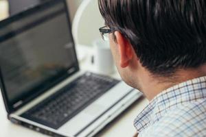 Foto des Geschäftsmannes, der in den Laptop schaut
