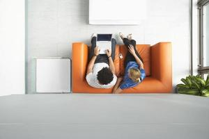 Paar mit Laptop auf orange Sofa im Büro