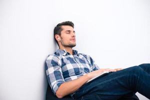 junger Mann in lässigem Stoff, der auf dem Taschenstuhl schläft foto