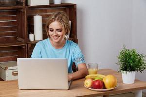 junge blonde Frau, die nach einer Rezeptinformation auf Laptop sucht foto