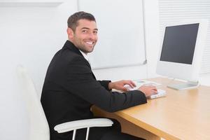 lächelnder Geschäftsmann, der an einem Schreibtisch arbeitet foto