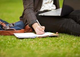männlicher Student der jungen Mode, der auf Gras sitzt foto