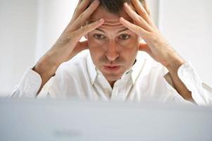 Ein Mann hält seinen Kopf in den Händen und schaut unter Stress foto