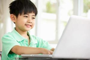 junger chinesischer Junge, der am Schreibtisch mit Laptop sitzt foto