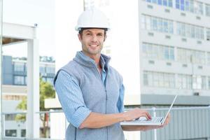 selbstbewusster männlicher Architekt mit Laptop foto
