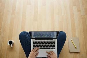 Mädchen sitzt auf Holzboden Laptop Kaffeetasse und Notizbuch foto