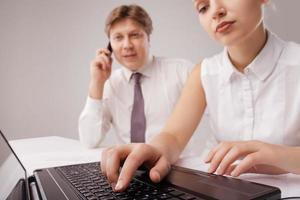 Mitarbeiter arbeiten mit Laptop und Handy foto