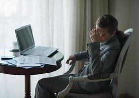 gestresste Geschäftsfrau, die im Hotelzimmer arbeitet foto