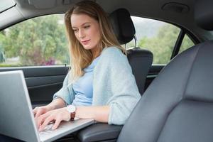 junge Frau, die auf dem Fahrersitz arbeitet foto