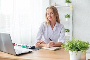 Porträt des Arztes, der in ihrem Büro arbeitet, das am Arbeitsplatz sitzt foto