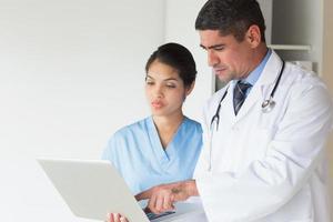 Arzt zeigt Laptop zur Krankenschwester foto