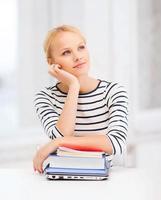 träumender Student mit Laptop, Büchern und Notizbüchern foto
