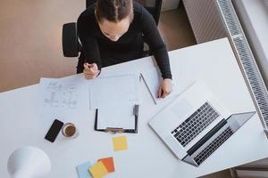 Geschäftsfrau, die Finanzdaten an einem weißen Schreibtisch analysiert