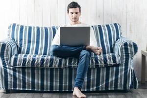 Mann arbeitet an einem Laptop foto