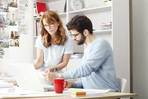 Geschäftskollegen, die an einem Laptop arbeiten foto