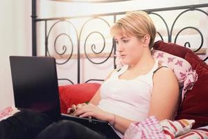 Frau mit Laptop stützt sich auf Kissen auf dem Bett foto