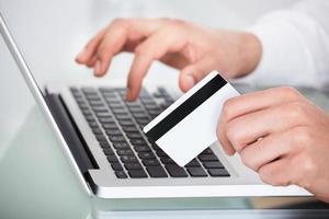 Mann einkaufen mit Kreditkarte und Laptop foto