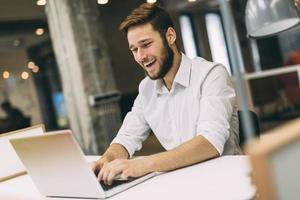 hübscher Mann, der in einem Büro arbeitet foto