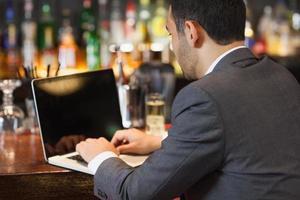 hübscher Geschäftsmann, der an seinem Laptop arbeitet, während er etwas trinkt foto