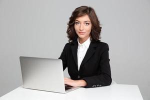 selbstbewusste schöne Geschäftsfrau, die mit Laptop arbeitet foto